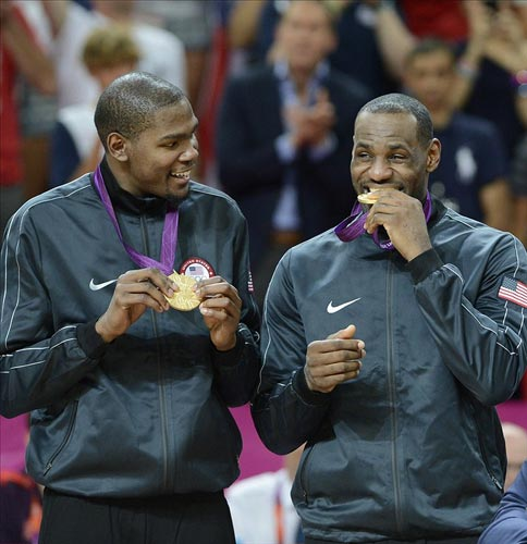 USA guard Kevin Durant watches USA forward LeBron James bite the gold medal