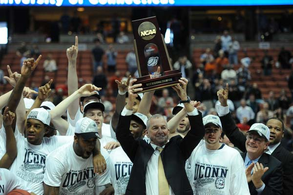UConn Head Coach Jim Calhoun holds up the trophy